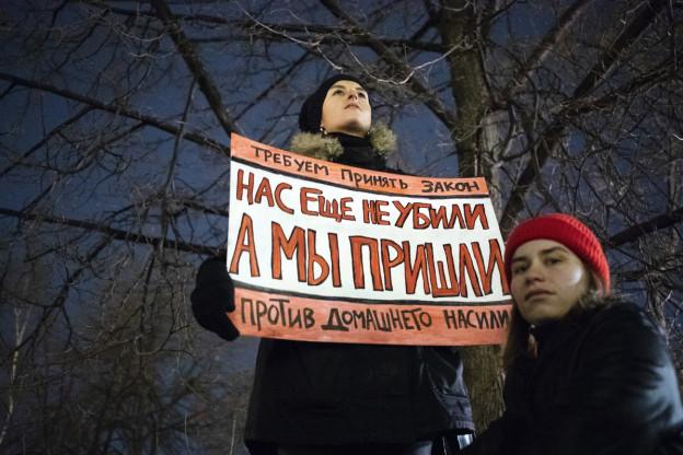 Zwei Frauen demonstrieren und fordern auf einem Plakat ein strengeres Gesetz gegen häusliche Gewalt in Russland.
