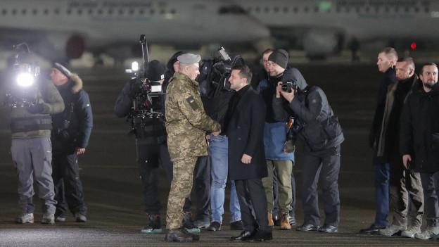 Zu sehen ist der ukrainische Präsident Wolodimir Selenski am Flughafen in Kiew. Er schüttelt einem militärisch gekleideten Mann die Hand, im Hintergrund ist ein Flugzeug. Die beiden sind umringt von Menschen, darunter von freigelassenen ukrainischen Gefangenen aus Russland.