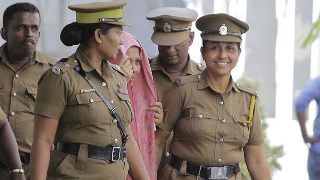 Strafvollzugsbeamte begleiten die Schweizer Botschaftsmitarbeiterin zum Gerichtsgebäude in Colombo, Sri Lanka.
