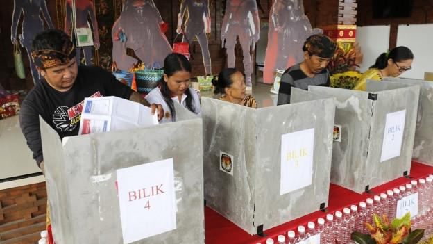 Menschen stehen an Wahlurnen.