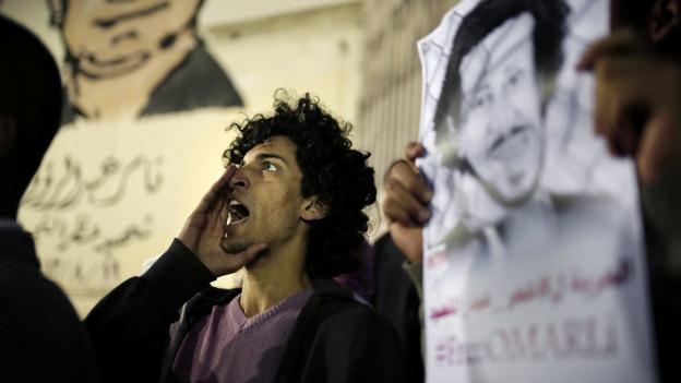 Journalisten protestieren mit Transparenten gegen die Inhaftierung des Fotojournalisten Shawkan in Kairo 2015.