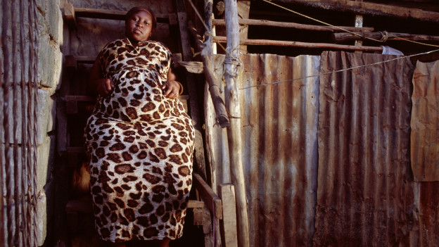 Eine junge, beleibte Afrikanerin sitzt auf einer Treppe