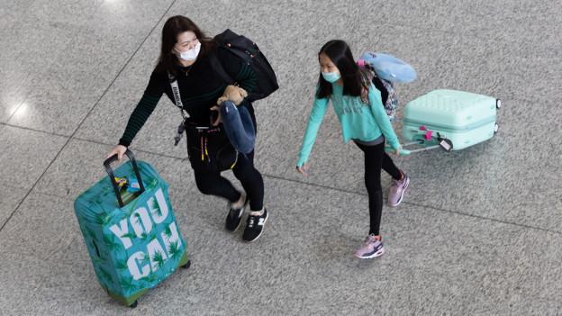 Das Bild zeigt zwei Frauen, die eine Maske tragen.