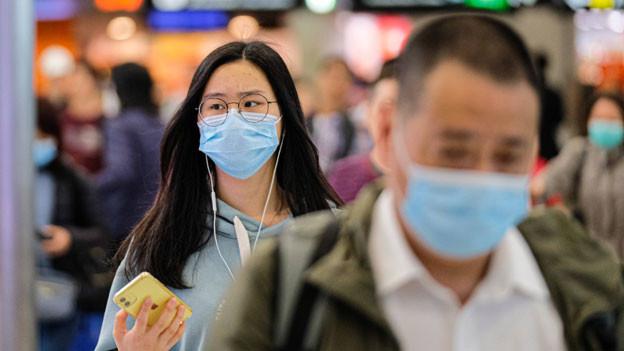 Reisende sind vorsichtig und viele setzen auf Reisen eine Schutzmaske auf.