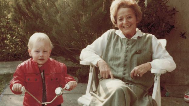 Eine ältere Frau und ein Kind auf einem Dreirad posieren vor der Kamera.