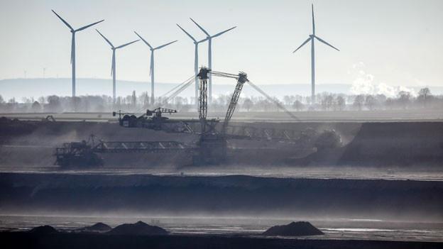 Jede Bank wird sich in Zukunft Gedanken machen, in welche Unternehmen sie investieren will. Auch Versicherungen ziehen sich schrittweise aus dem Geschäft z.B. mit Kohle-Kraftwerken zurück. Bild: Braunkohletagebau in Jüchen, Nordrhein-Westfalen, Deutschland. Im Hintergrund stehen Windräder.