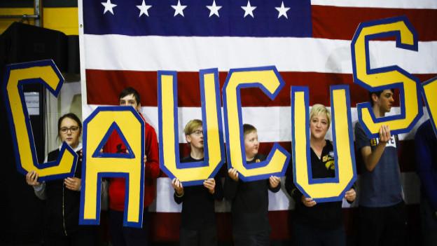 Anhänger halten das Wort «Caucus» in die Höhe