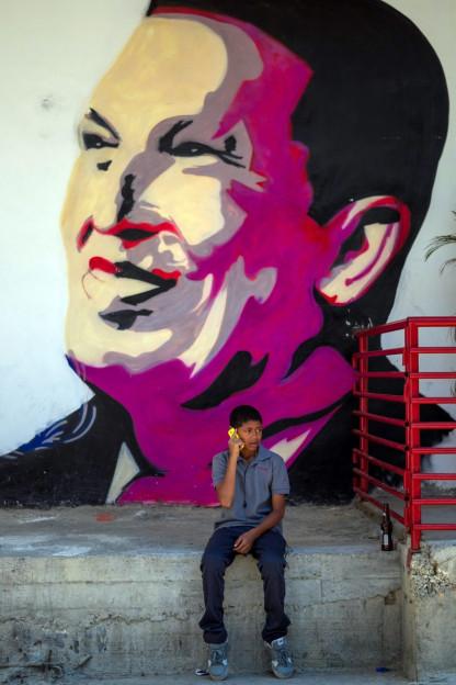 Ein Knabe sitzt vor einem Bild Maduros.