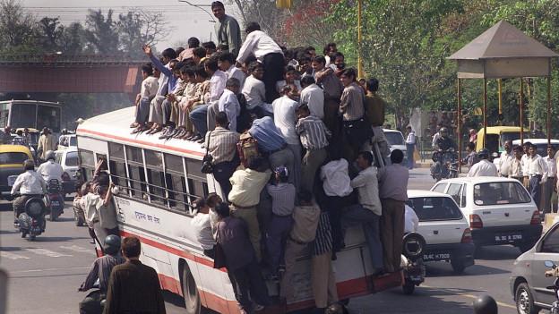 Völlig überladener Bus in einer Grossstadt in Indien.