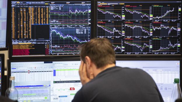 Ein Börsenhändler an der Börse Frankfurt blickt auf seine Monitore.
