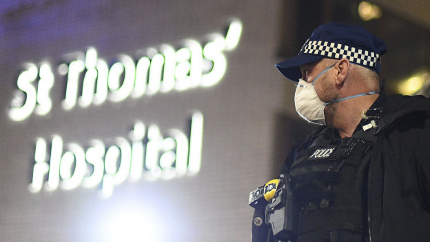 """Ein Polizist mit Schutzmaske steht vor einem Gebäude, dass mit """"St. Thomas' Hospital"""" angeschrieben ist."""