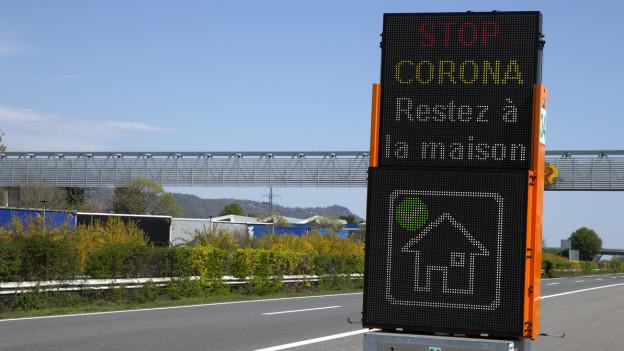 Französisches Warnschild zu Corona auf leerer Autobahn.