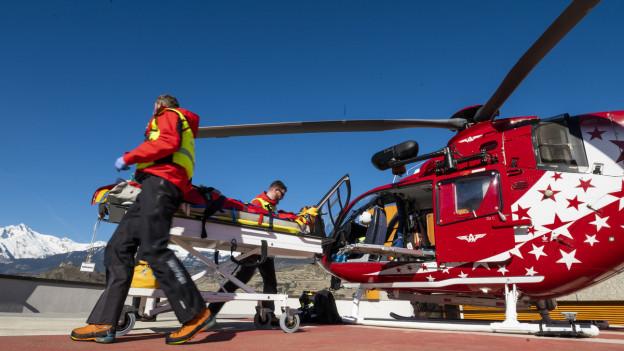 Rettungskräfte der Walliser Fluggesellschaft Air Glaciers bergen einen verletzten Skifahrer.