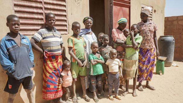 Geflüchtete Frauen und Kinder, die sich vor einer Unterkunft aufgestellt haben.
