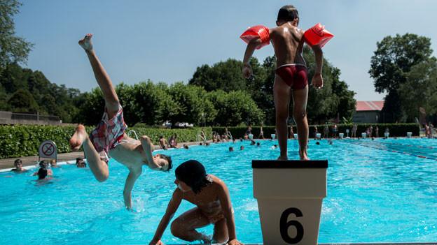 Kinder erfrischen sich im Schwimmbad in Mendrisio.