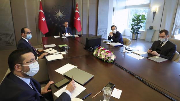 Auf dem Bild zu sehen ist die türkische Regierung, bestehend aus fünf Männern. Alle bis auf Präsident Erdogan tragen Schutzmasken. Sie sitzen an einem Holztisch.