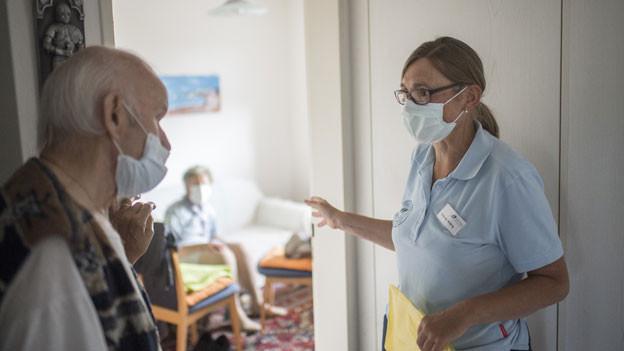 Eine Spitex Pflegefachfrau spricht mit dem Mann einer Kundin, aufgenommen während der Coronavirus-Pandemie.