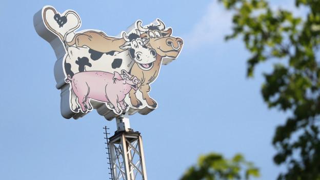 Das Bild zeigt ein Logo der Schlachterei Tönnies. Es besteht aus einem Rind, einer Kuh und einem Schwein. Das Logo ragt in den Himmel.
