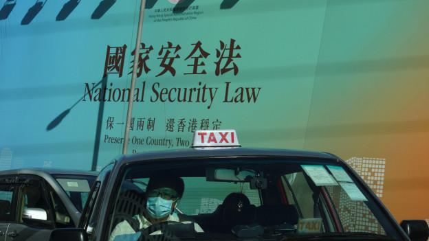 Ein Taxi in Hong Kong fährt an einem Plakat vorbei, das sich mit dem umstrittenen Sicherheitsgesetz befasst
