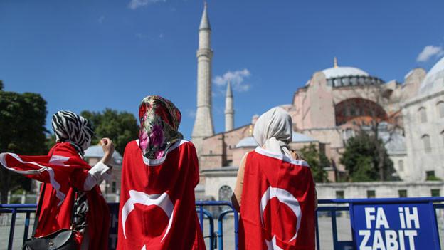 Menschen, umhüllt mit einer türkischen Flagge, freuen sich,  dass das 1500 Jahre alte Unesco-Weltkulturerbe Hagia Sophia in Istanbul, Türkei, in eine Moschee umgewandelt werden kann.