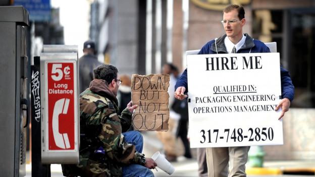 Das Bild zeigt einen Arbeitslosen in Indianapolis mit dem Schild und der Aufschrift «Stellt mich an».