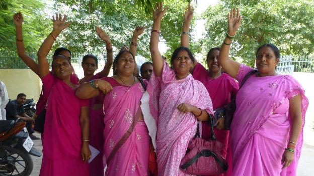 Das Bild zeigt acht Frauen der Gulabi-Gang in ihren pinkfarbenen Saris auf einer Strasse unter einem Baum.