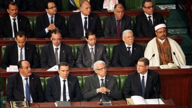Das Bild zeigt die neue tunesische Regierung, die im Parlamentssaal sitzt - in drei Reihen hintereinander.