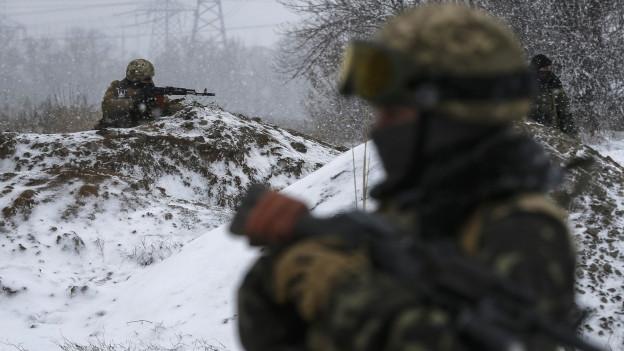 Im Vordergrund ist unscharf ein Soldat zu erkennen, im Hintergrund ein Schütze mit einem Maschinengewehr auf einem Schneehaufen.