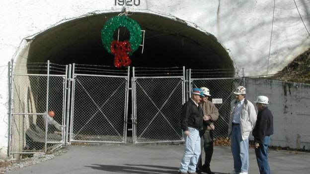 Tunnel führt in den Berg in eine Kohlemine, davor ein Gitter und eine Gruppe von Männern mit Helmen