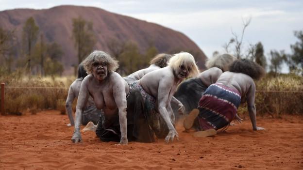 Aboriginal-Frauen führen vor dem Berg Uluru (Ayers Rock) einen traditionellen Tanz auf.