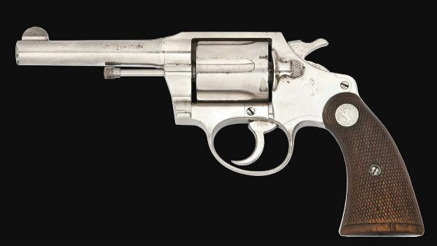 Nickel-farbener, leicht ramponierter Revolver mit braunem Beschlag am Griff.