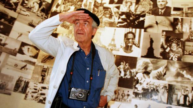 Rene Burri blickt in die Ferne. Im Hintergrund sind seine Bilder zu sehen.