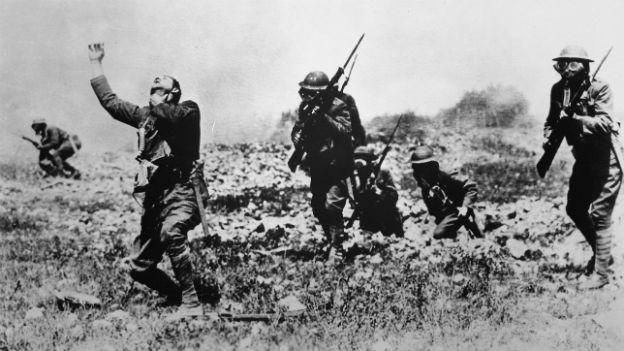 Das alte Bild in schwarz-weiss zeigt drei Soldaten bei einem Giftgasangriff. Einer hält sich die Hand vors Gesicht.