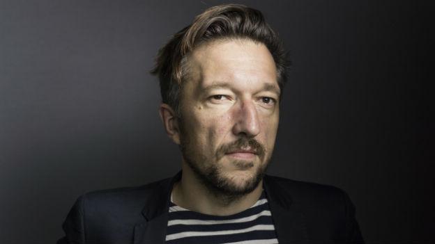 Porträtaufnahme des Schweizer Schriftstellers Lukas Bärfuss vor einem grauen Hintergrund.