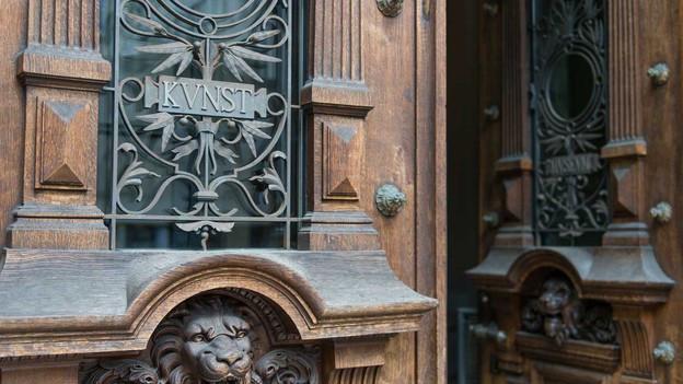 Das Bild zeigt die alte, grosse Tür des Kunstmuseums Bern mit dem Wort Kunst aus Eisen.