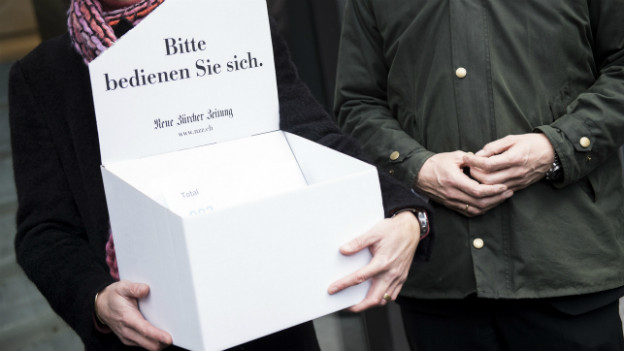 In einem Karton mit NZZ-Logo liegen gesammelte Unterschriften gegen die Schliessung des NZZ-Druckzentrums.