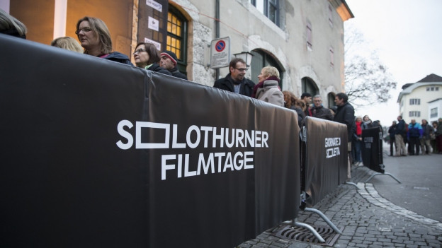 Das Bild zeigt Leute, die in Solothurn auf Einlass in eine Filmvorführung warten - hinter einer schwarzen Abschrankung mit weissem Aufdruck: Solothurner Filmtage.