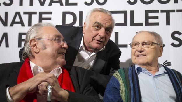 Das Bild zeigt den Regisseur Paul Riniker zwischen seinen beiden Hauptdarstellern Jörg Schneider und Mathias Gnädinger