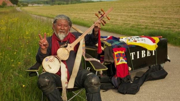 Der Musiker Lothen Namling sitzt auf einem schwarzen Sarg, Symbol für Lage in Tibet.