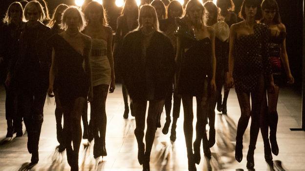 Mehrere dünne Models laufen über einen Catwalk in Paris.