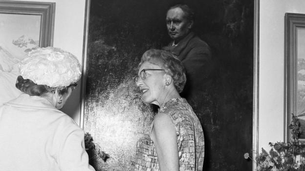 Zwei Frauen vor dem Gemälde eines Mannes.