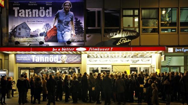 Eine Menschenschlange wartet vor der Kinokasse um einen Schweizer Film zu sehen.
