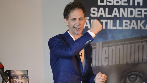 David Lagercrantz anlässlich einer Pressekonferenz, er schwingt seine rechte Faust zu einer Art Siegerpose.