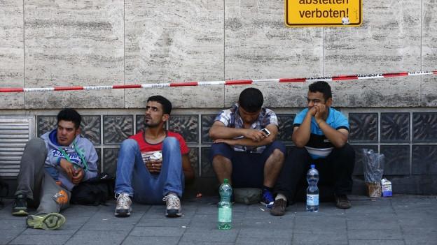 Vier junge Männer sitzen auf dem Trottoir, an eine Hauswand gelehnt.
