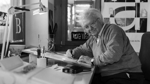 Der Grafiker und Schriftenmaler Adrian Frutiger sitzt an seinem Schreibtisch und kreiert Schriften