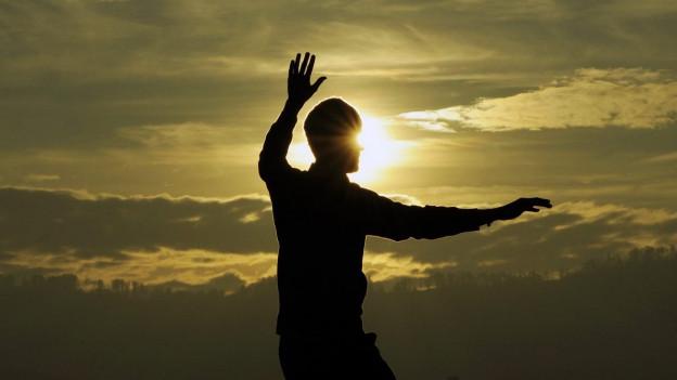 Man sieht vor sonnigem Himmel eine Silhouette, welche eine Übung macht.