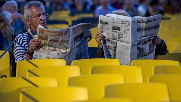 Zwei Personen sitzen in den gelben Festival-Stühlen und lesen in einer Zeitung.
