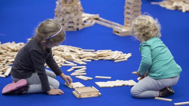 Zwei Kleinkinder spielen an der Suisse Toy in Bern mit Holzklötzen auf einem blauen Teppich (10. Oktober 2016).