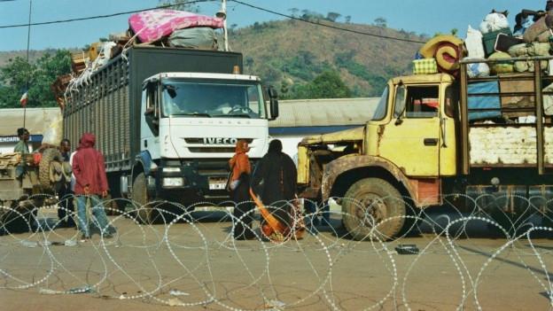 Aus dem Film «Cahier africain»: Vollbepackte Lastwagen stehen auf einem sandigen Platz.