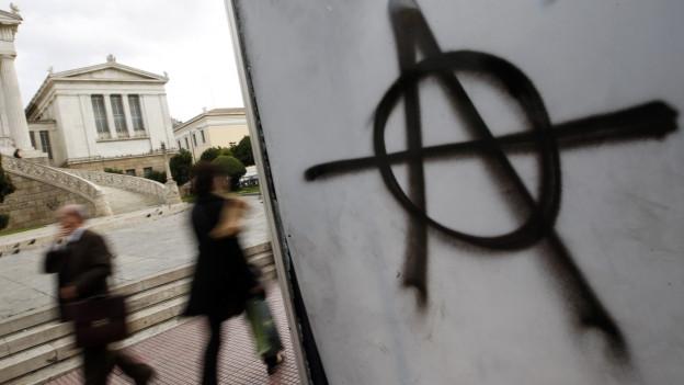 Ein Anarchie-Symbol wurde auf eine Bushaltestelle in Athen gesprayt.